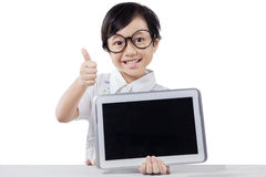 Child shows tablet and thumb up in studio Stock Photo