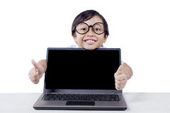 Child shows thumbs up with empty laptop screen Stock Photo