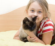 Child with a Siamese. Cat lying on a bed of yellow color Stock Photos