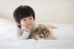 Child and siberian husky puppy lying on white bed. Cute asian child and siberian husky puppy lying on white bed Royalty Free Stock Image