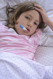 Child sick at home. Using thermometer Royalty Free Stock Photo