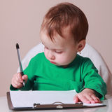 Child signs a contract (humorous picture) Royalty Free Stock Photography