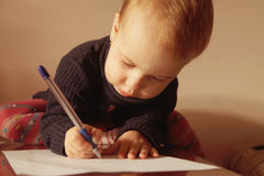 Child signs a contract (humorous picture, close up) Stock Photos