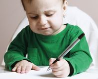 Child signs a contract humorous picture. Close up Stock Photos