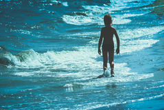 Child silhouette against the sea. Instagram stylisation. 1. Silhouette of young boy who walking by the sandy beach. Instagram stylisation Stock Photos