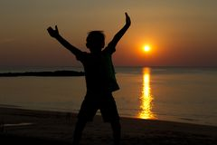 Child silhouette at the beach with sunset background stock images