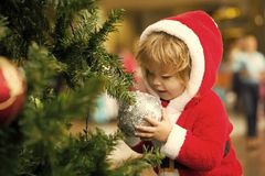 Child with silver ball on Christmas tree wearing santa costume stock photo