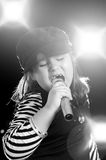 Child Singing. A little girl is singing into a microphone with flashes and lights in the background Royalty Free Stock Photos