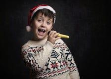 Child singing Christmas carol at Christmas. On black background Stock Photography