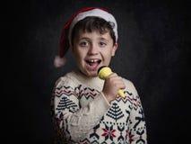 Child singing Christmas carol. At Christmas  villancico Stock Photography