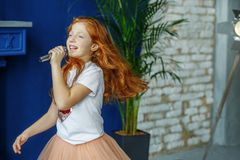 The child sings the song in the microphone. Very long hair. The. Concept is childhood, lifestyle, music, singing, listening, hobbies royalty free stock photography
