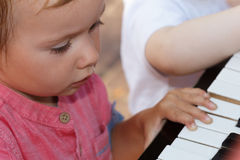 Child sings a song and plays piano, happy childhood. Child sings a song and plays piano, happy portrait, childhood Stock Photos