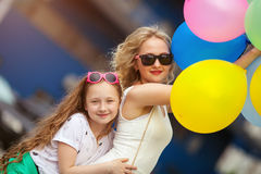 Child and sister in trendy sunglasses having fun outdoors with lots of colorful balloons. Hugging and laughing.happy family life royalty free stock photos