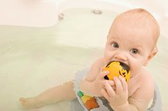 Child sit in the bathtube nibble rubber toy with b Stock Photos