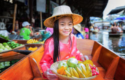 Child sit on the boat and hold the fruit basket Stock Images