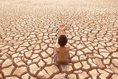 Child sit on cracked earth Royalty Free Stock Photos