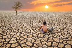 Child sit on cracked earth. In the arid area Royalty Free Stock Photography
