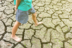 Child sit on cracked earth in the arid Stock Photo
