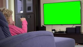 Child sit in front of a tv and watch a children show on. Green chroma key screen stock footage