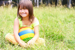 The child sit on a grass Stock Image