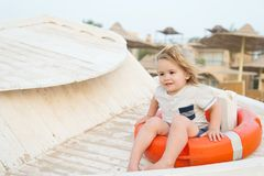 Child sit in ring buoy on sunny day. Little boy with lifebuoy on tropical beach. Kid with blond hair have fun outdoor. Summer vaca. Tion and activity. Safety Stock Photo