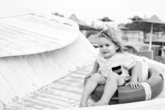 Child sit in ring buoy on sunny day. Little boy with lifebuoy on tropical beach. Kid with blond hair have fun outdoor stock photo