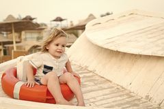 Child sit in ring buoy on sunny day. Little boy with lifebuoy on tropical beach. Kid with blond hair have fun outdoor royalty free stock photos
