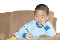 A child sit in sofa and writing Royalty Free Stock Photo