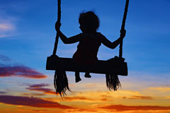 Child sit on swing on colorful sunset sky background Royalty Free Stock Photography