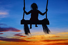 Child sit on swing on colorful sunset sky background. Black silhouette of baby girl flying high with fun on rope swing on blue orange sunset sky background Royalty Free Stock Photos