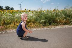 Child sits on asphalt road Royalty Free Stock Image