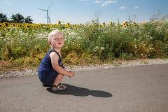 Child sits on asphalt road Royalty Free Stock Image