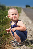 Child sits on asphalt road Royalty Free Stock Photos