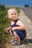 Child sits on asphalt road Royalty Free Stock Photos