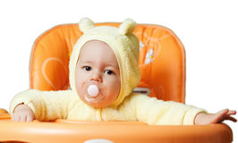 The child sits in a baby chair waiting to be fed Stock Photography