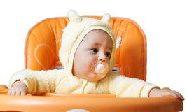 The child sits in a baby chair waiting to be fed Stock Photo