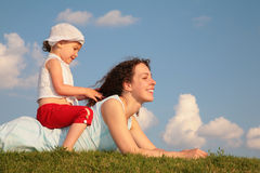 Child sits on back of mother lying on grass Royalty Free Stock Photo