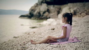 Child sits on the beach of the Adriatic Sea and throwing stones into the water. stock video footage