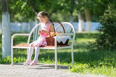 A child sits on a bench with a basket of bread. royalty free stock images