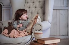 The child sits in big a chair. The Scandinavian style. The child sits in big a chair. The Scandinavian winter and the cozy atmosphere in the house royalty free stock images