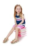 The child sits on the books Stock Photo