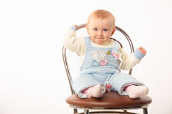 Baby sitting on a chair, studio. A child sits on a chair, the girl dressed in overalls Stock Photos