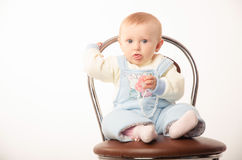 Baby sitting on a chair, studio Stock Photos