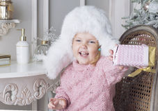 The child sits on a chair and holding a gift. The girl dressed in a white fur hat Stock Image