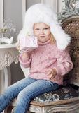 The child sits on a chair and holding a gift. The girl dressed in a white fur hat Royalty Free Stock Images