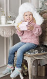 The child sits on a chair and holding a gift. The girl dressed in a white fur hat Stock Photo