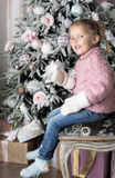 The child  sits on chair near Christmas tree. Smiling girl wearing warm mittens Royalty Free Stock Images