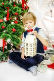 The child sits at the Christmas tree and plays the Christmas hom Stock Photos
