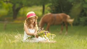 Child sits in a clearing, turns over the torn wild flowers and makes a bouquet from them. Slow motion stock video footage