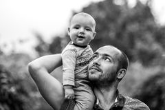 Child sits on dad's shoulder and smiling. Black and white a photo stock photo
